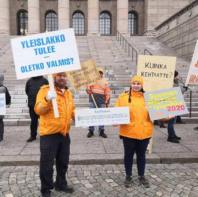 """Kuva mielenosoittajista ja heidän kylteistään. Yhdessä lukee """"Yleislakko tulee, oletko valmis?"""". Kuvaaja Sippo Kähmi."""