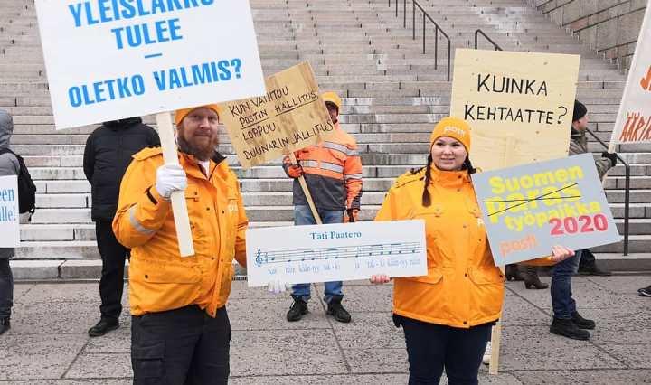 """Kuva mielenosoittajista ja heidän kylteistään. Yhdessä lukee """"Yleislakko tulee, oletko valmis?"""""""