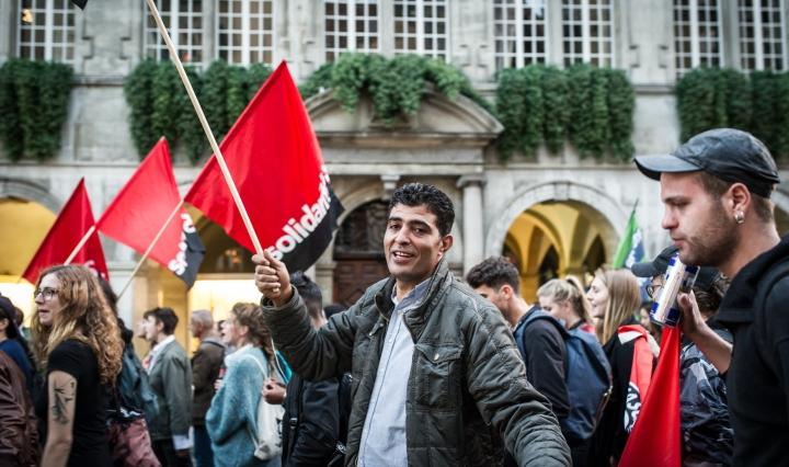 """Mielenosoittajia punamustien lippujen kanssa, joissa lukee """"solidaarisuus"""". Yksi mielenosoittaja katsoo kameraan ja hymyilee."""