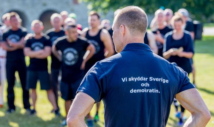 """Ruotsalaisia poliiseja. Etualalla selin yksi henkilö, jonka paidassa lukee """"Vi skyddar Sverige och demokratin."""""""