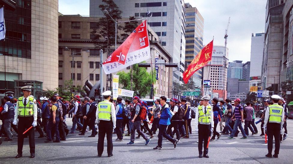 Ihmisiä marssimassa kadulla. Näkyvissä kaksi punaista lippua, joissa koreankielistä tekstiä. Etualalla neljä järjestyksenvalvojaa keltaisissa huomioliiveissä.